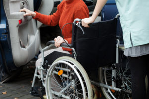 Caregiver helping disabled lady get into the car